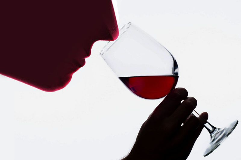 Image of a person inspiring the aroma of wine in a glass
