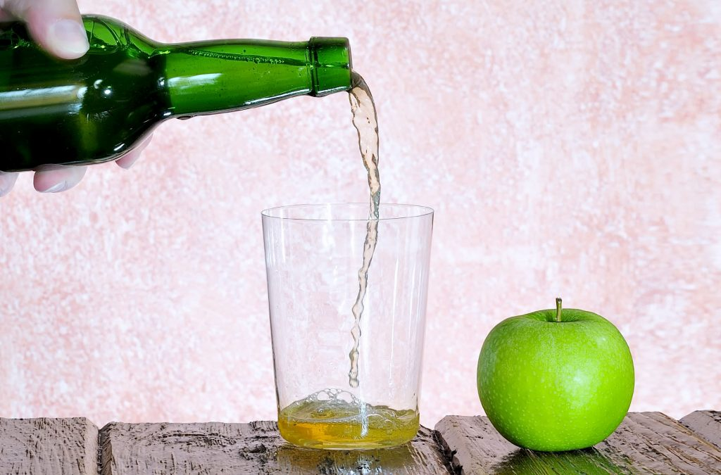 Image of a bottle pouring cider into a glass with an apple next to it